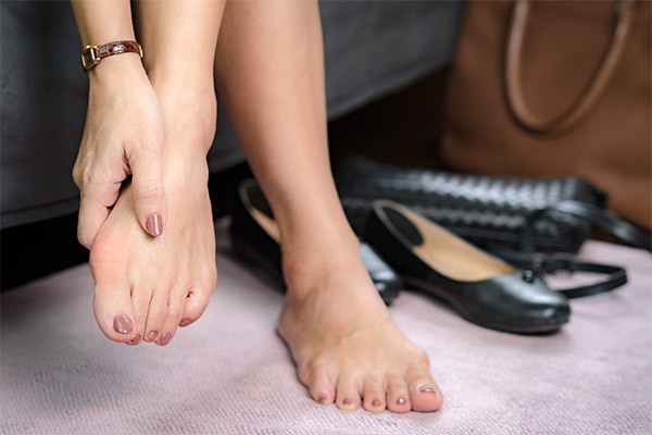 woman holding foot with bunion